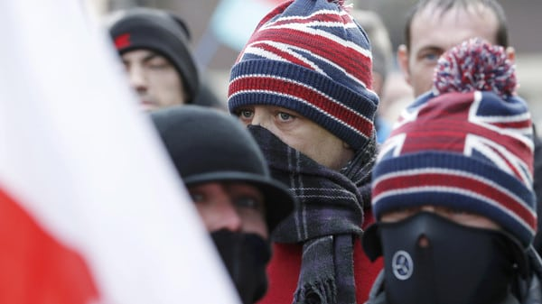Men with their faces covered attend a demonstration by supporters of the Pegida movement in Newcastle, northern England
