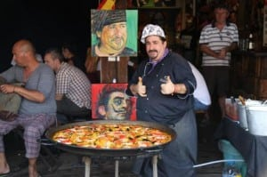 A chef at a food shop in Chatuchak market poses with a pan of paella.